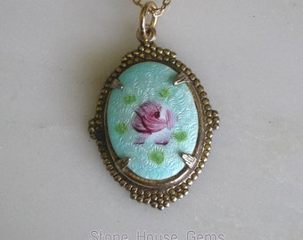 Blue Guilloche enamel pendant with a pink flower in the center.