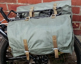 A pair of canvas pannier bags in olive green 80s vintage ex-army bicycle panniers with shoulder strap