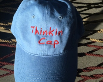 "Thinkin Cap - Light Blue w/Red Lettering - Reverses to Say ""Not Thinkin"" on the Back"