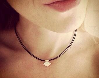 Gold rhombus charm choker necklace on adjustable black cord.