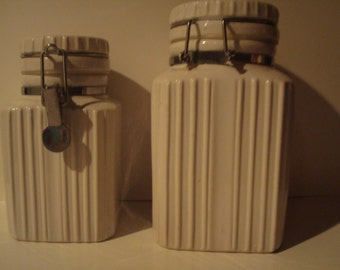 Two white locking canisters