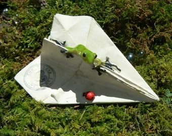 Miniature paper airplane with frog and ladybug