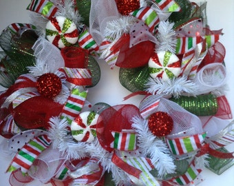 Festive red, green and white Christmas deco mesh wreath with candies and beaded bulbs.