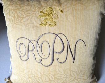 monogram embroidered pillow with metallic gold lion on gold damask trim and tassels