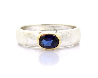 Blue sapphire ring set in gold and a matte silver band