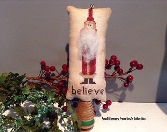 "Primitive cross-stitched ""believe"" Santa  on a vintage wood bobbin"