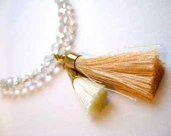 Tassel necklace in white and light peach, with large clear crystals and small glass beads