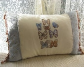 Pillow cushion cover cross stitch panel depicting butterflies connected with baby blue and shades of brown floral with matching tassel trim.