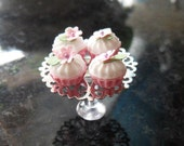 4 cupcakes with flower decoration on a lovely cake stand