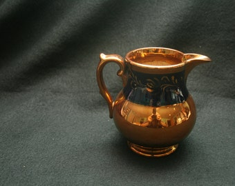 Small Copper colored pitcher with navy blue band