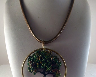 Brass wire sculpted tree in circle, painted, on chain.