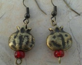 Beautiful pendant earrings with a chunky brass pomegranate charms and small red glass beads on brass coated earring wire.