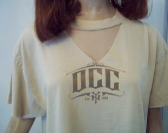 UPCYCLED OCC T SHIRT...tan with brown graphic...est 1999...cut up front and back..sz lg