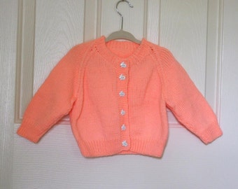 Hand Knitted - Peach Childs Cardigan with White Bunny Buttons.