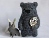 A dark grey bear brooch