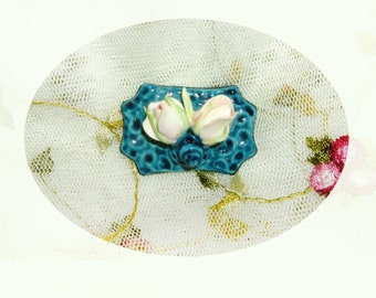 Deep Turquoise looking similar to cloisonne topped with two pink rosebuds