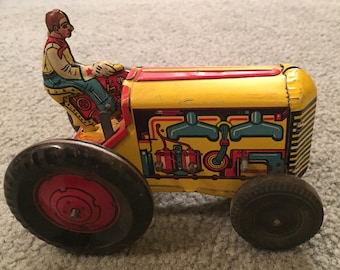 Vintage Man riding tractor wind up toy