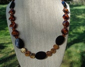 "Made-to-order, Exquisite 20.5 "" necklace with jet ovals, shell disks, and amber beads."