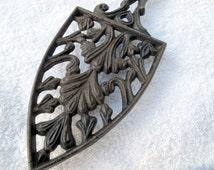 Vintage cast iron iron shaped trivet / cutwork style footed trivet / cast iron kitchen decor