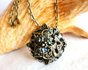 Dragon necklace, round pendant with blue glass jewel, bronze dragon and bronze filigree accents .