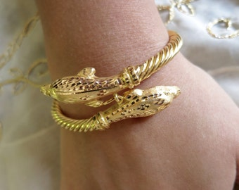 22K Yellow gold twisted wire with dolphins flexible bangle.