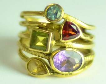 5 Gem stones of different shapes and colour have been set in brass to create this stack like ring.