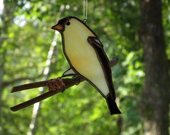 Goldfinch in stained glass on a branch (a bird on a branch)
