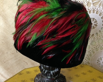 Vintage black felt hat with read and green feathers.