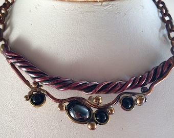Red copper wire necklace with brass accents, and hematite and black onyx stones, on a brass chain.