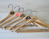 collection of vintage wooden pants, coats, suit hangers with store labels