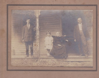 early 1900s cardboard photo. granny in rocker with family standing on the porch of the old home place.