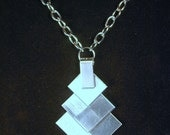 Distinctive stacked rectangle pendant on long silvered chain.