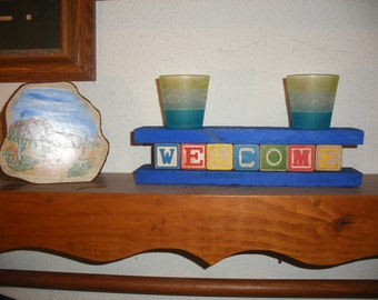 Wooden Colored Letter Blocks Spelling Welcome Framed in Blue Shelf Sitting Decor Rustic Toy Word Blocks