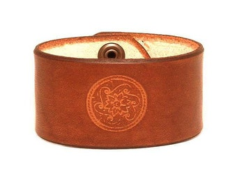 Embossed leather bracelet with a concho pattern