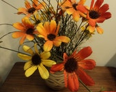 Silk flowers in clay jar/ vibrant colors in orange, red, yellow/terra cotta jar