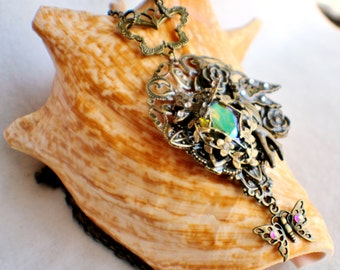 Angel pendant with layers of bronze floral filigree, leafs and roses surrounding a glass jewel.
