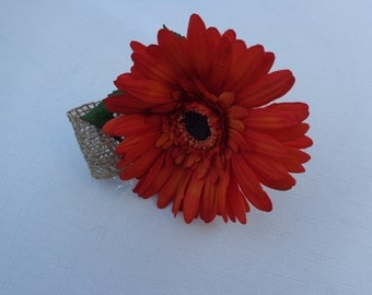 Boutonniere designed with a orange gerber daisy trimmed with burlap