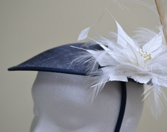 Navy fascinator hat with an ivory feather mount and two ivory feather flowers