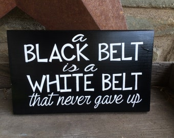 A black belt is a white belt that never gave up - karate inspired sign