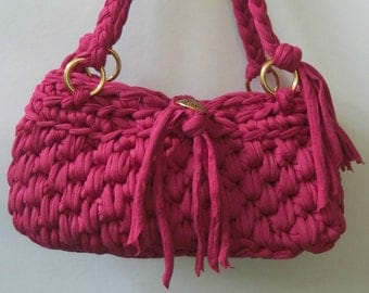 Pink shoulder bag/handbag crochet from t shirt yarn. Has braided shoulder straps and a bow closure.