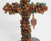 Copper Cross mounted in Hematite.  Beaded with Copper, Madagascar Hematite, Agate and Crystal Beads with a Love Charm.