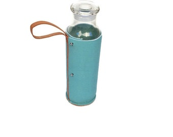 Glass water bottle wrapped in thick blue leather with with glass stopper for hydration, smoothies or juice handmade in Portland Oregon USA