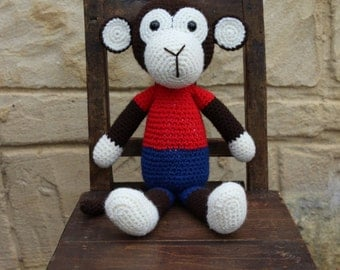 Handmade, crocheted toy monkey for children and babies in brown, red, blue and cream