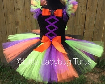Little Witch Halloween Tutu Dress. Orange, Black, Green and purple tulle dress with corset style top. Available in toddler and girl sizes.