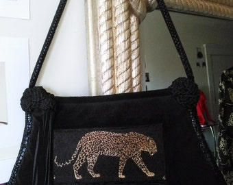 Elegant black suede handbag with walking cheetah animal print