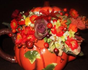 Autumn / fall pumpkin teapot with seasonal silk floral arrangement with the teapot top nestled on top