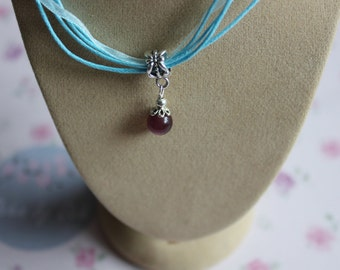 A blue ribbon necklace with a deeep plum/purple pendant