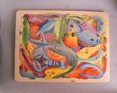 Wooden hand cut puzzle with ocean fish, in a tray