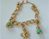 Vintage Monet Charm Bracelet with Charms Buddha Cat Lion Gold Tone Green Glass Fancy