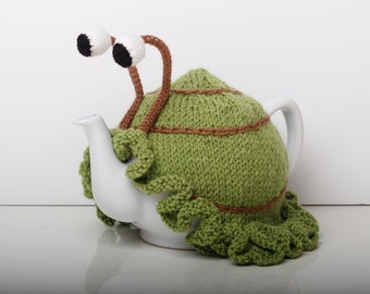 Knitted green snail tea cosy with frilly bottom. Washable fits 1 litre teapot. Available with or without teapot.